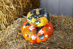 Painted pumpkins. A snapshot with 2 pumpkins covered with face and body painting placed on a straw bale Stock Photos