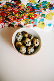 Painted quail eggs in a bowl  on colorful child drawing Royalty Free Stock Image