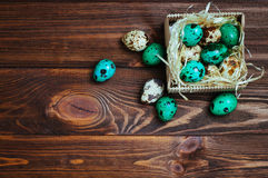 Painted quail eggs in the box over wooden background Royalty Free Stock Images