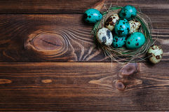 Painted quail eggs in natural nest over rustic wooden background Stock Photo