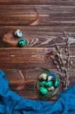 Painted quail eggs in natural nest with willow branches over woo Stock Photos