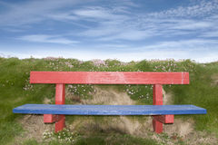 Painted red and blue bench. Red and blue bench positioned at the edge on top of a cliff stock photos