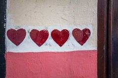 Painted red hearts. Red hearts painted on a colorful wall background Stock Image