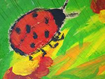 Painted red ladybird on old wooden desk in street royalty free stock image