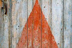 Painted red triangle on the old wooden door with handle Royalty Free Stock Photography