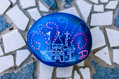 Painted rock of a castle and dotted lines. A small rock is painted vivid metallic blue and has a picture of a castle and fireworks with a capital D representing stock photo