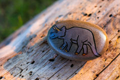A painted rock with a picture of a dinosaur Royalty Free Stock Photo
