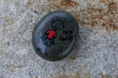 Painted rock with picture of a stick figure and words stating `Hey buddy`. Small stone painted with a stick figure boy wearing a red shirt and the words `Hey royalty free stock photo