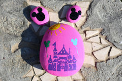 Painted rocks of a castle and Mickey Mouse heads. Three painted pink rocks representing Disneyland. Two small rocks are pink with black silhouette of Mickey royalty free stock photo
