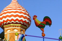 Painted rooster on the holiday of Maslenitsa. Cock of the fairy tale on a pole among the domes of the Church of the Intercession on the Moat on the red square Royalty Free Stock Photography