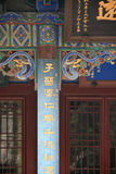 Painted and sculptured patterns decorate the facade of a temple in China stock images