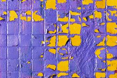 Painted shabby mosaic tiles on the facade of a house. Purple and yellow colors royalty free stock photos