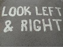 A painted sign on a concrete foot path telling people to look left and right. For traffic royalty free stock photo