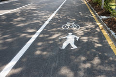 Painted signs on asphalt for pedestrian and bicycle lanes Royalty Free Stock Image