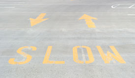Painted slow sign with arrows on concrete Royalty Free Stock Image
