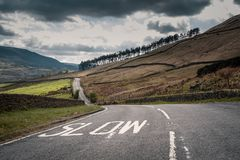 Painted Slow warning sign on winding country road in England. White Slow warning sign painted on a winding rural tarmac road in the countryside of Derbyshire royalty free stock photo