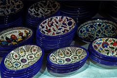Painted souvenir plates on the counter in the store of Jerusalem, Israel. National ornament on a plate with blue edging.  royalty free stock photography