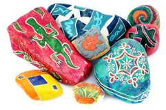 Painted stones. Four stones decorated with colorful shape against white background royalty free stock photo