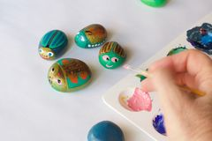 Painted stones as beetles handmade on a white background. Fun activity for children stock image