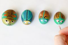 Painted stones handmade as beetles on a white background. Four painted stones handmade as beetles on a white background royalty free stock photo
