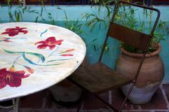 Painted table and metal chair with potted plant and blue wall Royalty Free Stock Photography