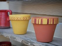 Painted terracotta pots. Hand painted terracotta planting pots on shelf stock photography