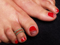 Painted Toe Nails. Photographe of Painted red Toe nails, with decoration Stock Images