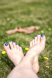 Painted Toes in the Grass. Crossed bare feet relaxing in dandelion spotted grass Royalty Free Stock Images