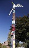 Painted totem pole in riverfront park Stock Photo
