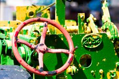 Painted Tractor. A green/yellow/red painted tractor weathered in the sun Royalty Free Stock Photography