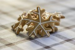 Painted traditional Christmas gingerbreads arranged on checkered tablecloth, group of snowflakes, white sugar icing. Painted traditional Christmas gingerbreads stock photography