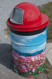 Painted Trash Can. With red top and field of flowers and blue sky Stock Images