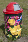 Painted Trash Can. With red top and field of flowers yellow and pink Stock Image