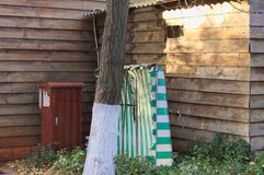 Painted tree near a wooden house, a container and a striped curtain Stock Image