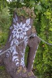 Painted tree stump in Zalipie, Poland. ZALIPIE, POLAND - October 7, 2017: A village in Poland known for a local custom of painting cottages and objects with stock images