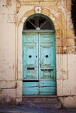Painted turquoise door Gozo Malta. To an old run down house Stock Image