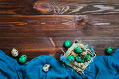 Painted turquoise quail eggs in the box over rustic wooden backg Royalty Free Stock Photos