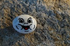 Painted white stone with a happy face Stock Photography