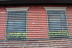 Painted windows. Metal security grate painted as red brick wall with windows and window boxes Royalty Free Stock Photography