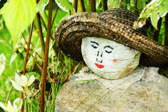 Painted woman face on rock. Original homemade garden decoration with round painted rock as a woman's face with straw hat hidden amongst the hedge plants Stock Photos