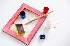 Painted wood picture frame with paints, sponge and paintbrush Royalty Free Stock Photo