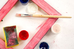 Painted wood picture frame with paints, sponge and paintbrush Royalty Free Stock Image
