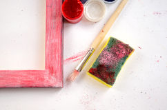 Painted wood picture frame with paints, sponge and paintbrush Stock Photo