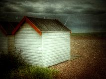 Painted wooden beach hut on shingle beach. Two painted wooden beach it's on a shingle beach Stock Photography