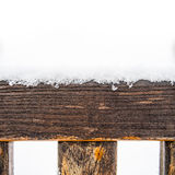 Painted wooden board and rungs covered with snow. Detail of weathered painted wooden bench covered in snow, top of timber, plank or board with rungs or spokes Stock Images