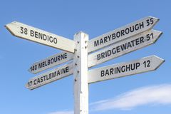 Painted wooden signpost at Maldon town centre showing distance and directions to surrounding towns in a blue sky. Painted wooden signpost at Maldon town centre stock photography