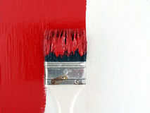 Close-up paint brush painting red color on white wooden wall, renovate and decorate old house. Paint brush painting red color on white wooden wall, renovate and stock image