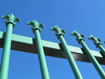 Painted Wrought Iron Fence. A green painted wrought iron fence with blu sky background royalty free stock photos
