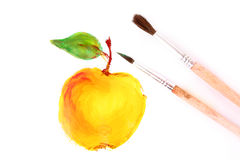 Painted yellow apple and brushes isolated Stock Image