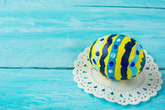 Нand-painted yellow Easter egg. With abstract design on a blue wood plank background. Easter background. Easter symbol. Copy space Stock Photos